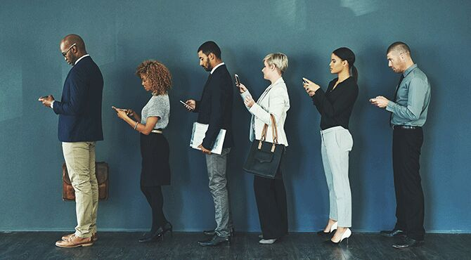 Young workers wait in queue on mobile phones