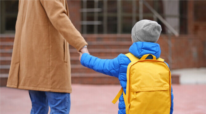 Image of small boy and parent at school drop off
