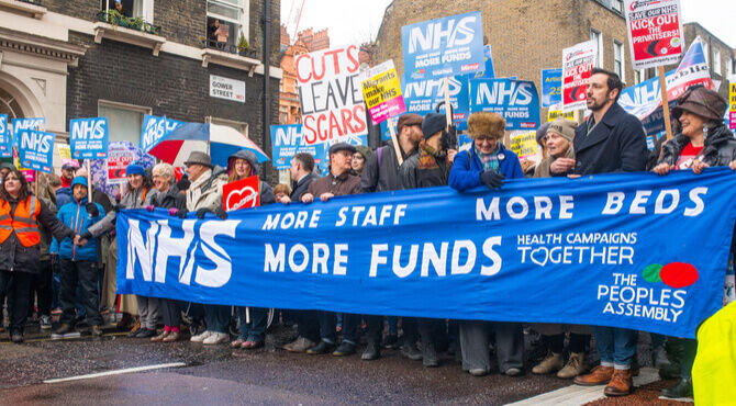 Image of February 2018 NHS crisis march with people and banners supporting migrants and against underfunding
