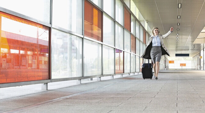 Image of business women running through an airport with a suitcase