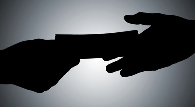Silhouetted handshake and cash