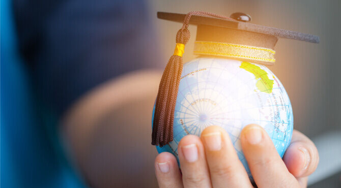 Image of globe in person's hand with mortarboard cap on