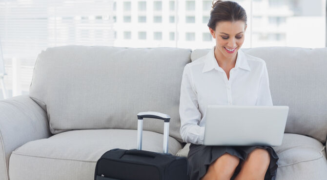 Business women with suitcase sitting on a sofa