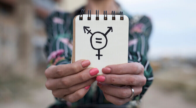 Image of person holding transgender symbol