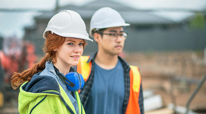 A young man and young woman apprentices on a construction job