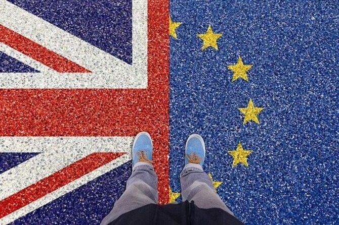 Image of EU and UK and a person standing with a foot on each