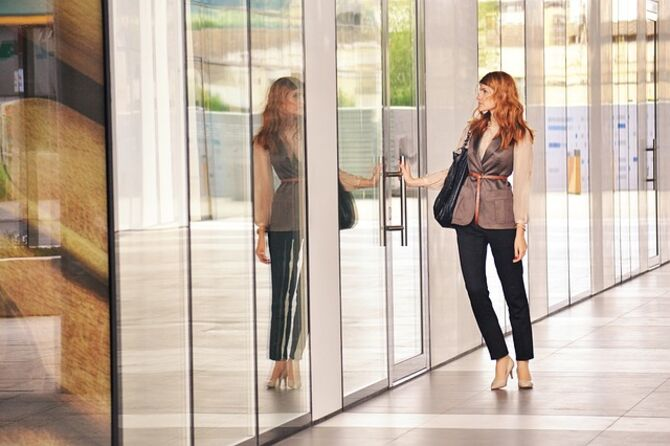 Image of woman reflected in glass opening door