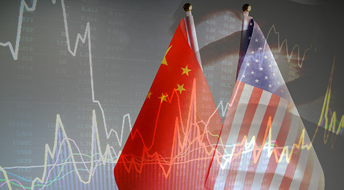 Chinese and American flags over a background showing financial markets