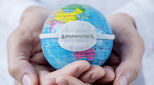 A globe encircled by hands with the word Coronavirus superimposed upon it