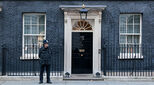 Photo of 10 Downing Street, home of the British Prime Minister, with a policeman standing guard outside