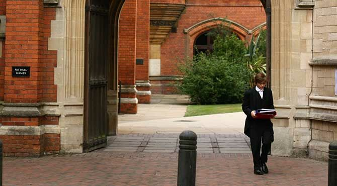 Eton College student pupil walks beneath an archway featuring a statue of Queen Victoria in the Meadow Lane entrance of Eton College, Windsor.
