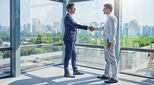 Two men shaking hands illustrates an article about repats and talent management