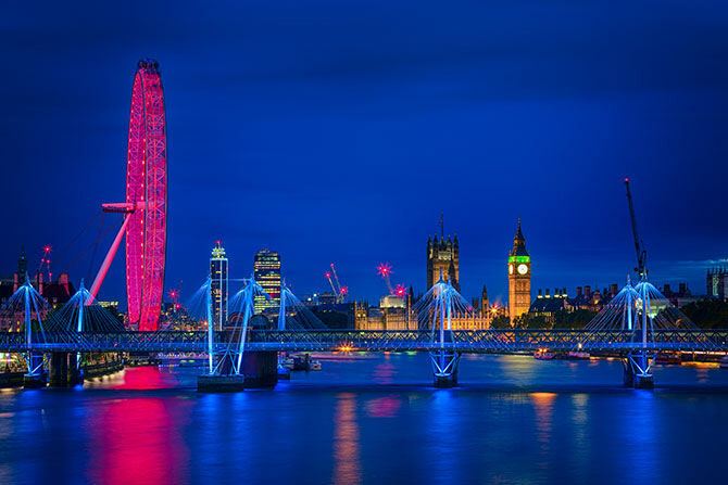 Image of the London skyline at night, featuring the Houses of Parliament and London Eye