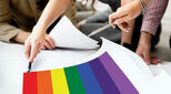 Pride flag on drawing board with people making plans