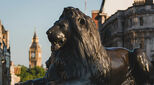 Landseer lions in Trafalgar Square with the Houses of Parliament in the distance, London