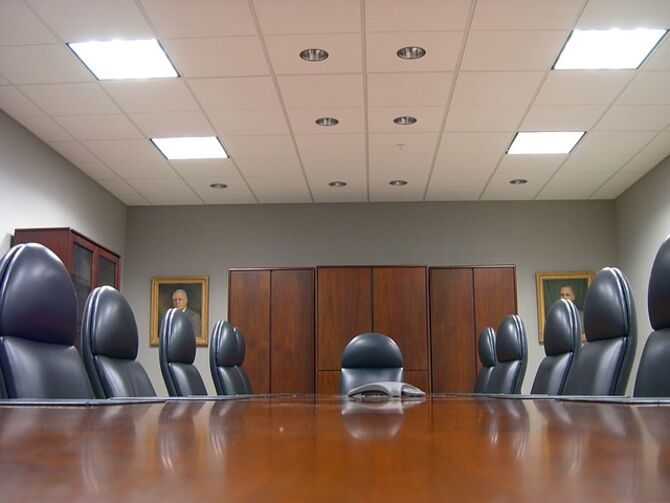 Image of empty board room with images of men in paintings on wall