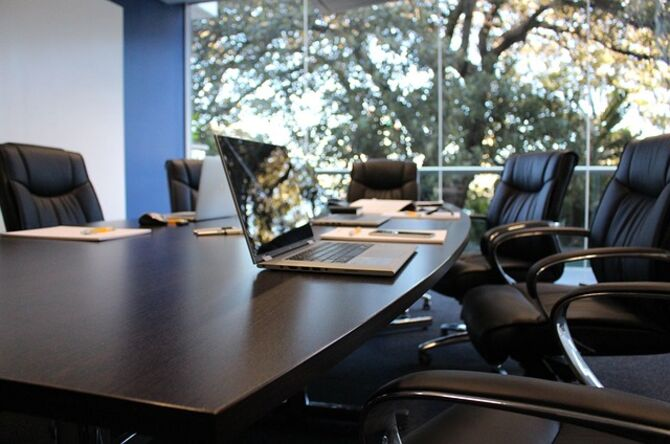 Image of boardroom empty except for a laptop
