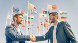 Two people shaking hands against background of flags