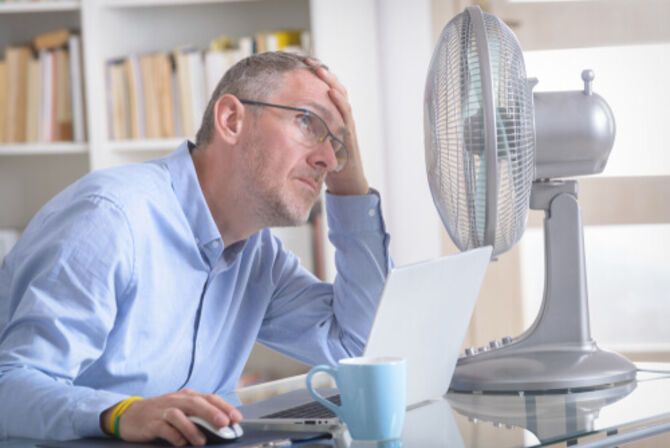 Image of man in office next to fan holding his head