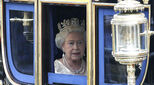 The Queen of England driving to Parliament in a carriage