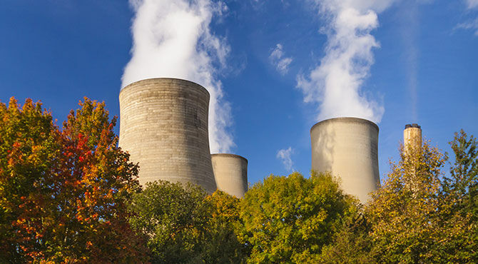 Image of a UK nuclear plant with trees with autumn leaves in the foreground