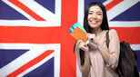 Union Jack flag with an international student standing in front of it holding a passport