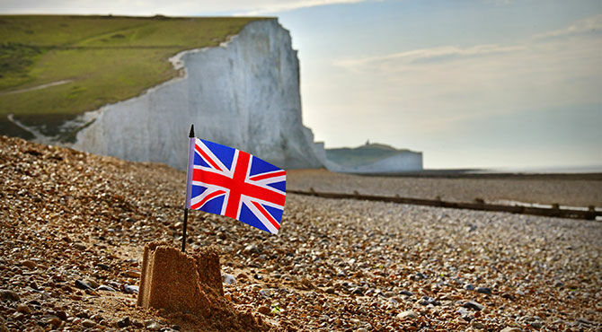A union jack flag in a sandcastle on a beach with the White Cliffs of Dover in the background
